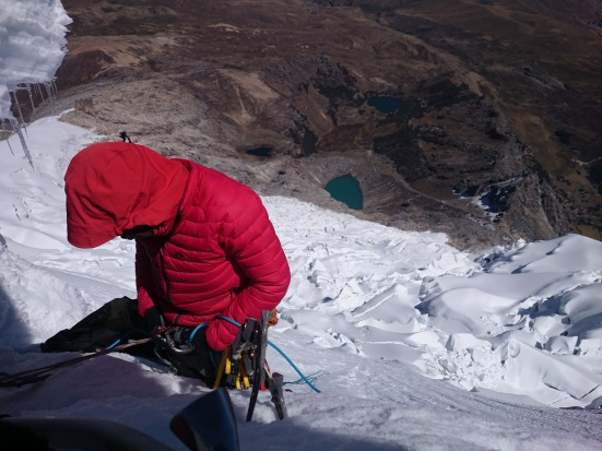Nick belaying right below the summit. (Artem Bylinskii photo, taken from the ice ledge under the cornice).